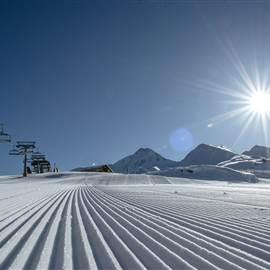 Prepared ski slope in detail in bright sunshine