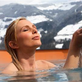 Woman in whirlpool in front of mountain panorama